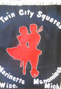 Dark banner with image of square dancing couple in red, and white lettering
